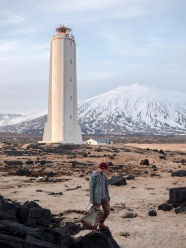 man-walking-near-lighthouse-and-snowy-mountain-4344695